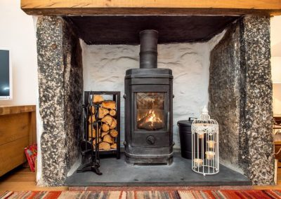 Woodburner within deep fireplace