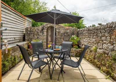 Sheltered table and chairs on patio in walled courtyard