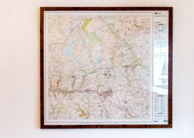 Ordnance Survey map of local area in frame on wall