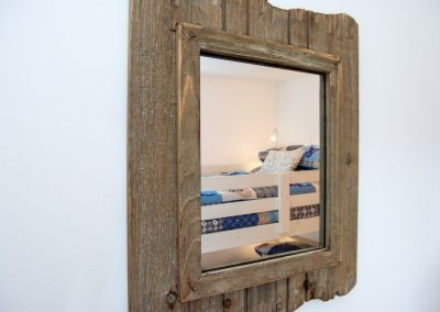 Reflection of bunk beds in rough wood mirror
