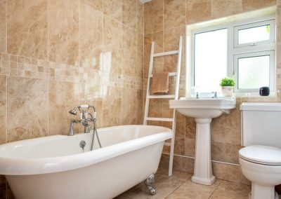 Standalone bath and white suite in tiled bathroom